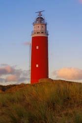The Eierland Lighthouse on the northernmost top of the Dutch island of Texel, Red lighthouse tower on the dunes with marram grass and golden sky during sunset as background, North Holland, Netherlands