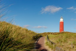 The Eierland Lighthouse on the northernmost top of the Dutch island with footpath, Red lighthouse tower on the dunes in summer under blue sky and white fluffy cloud, Texel, North Holland, Netherlands.