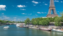 The Eiffel tower from Bir-Hakeim bridge over the river Seine in Paris. Ship and boats on river at sunny summer day