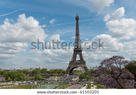 The Eiffel Tower, in Paris, France, as seen from Trocadero, with blue sky and clouds, purple flowering trees, sunlight, and crowds below.