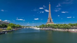 The Eiffel tower timelapse  from Bir-Hakeim bridge over the river Seine in Paris. Ship and boats on river at sunny summer day