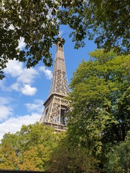 the eiffeltower behind some green trees