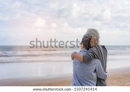 The elderly couples embraced at the seaside.The elderly couples embraced at the seaside.An old couple hugged by the sea.Mature couples relax at the seaside on holiday.