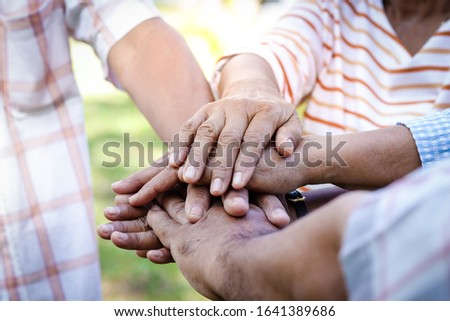 The elderly group join hands Have a happy life after retirement. Elder community concept