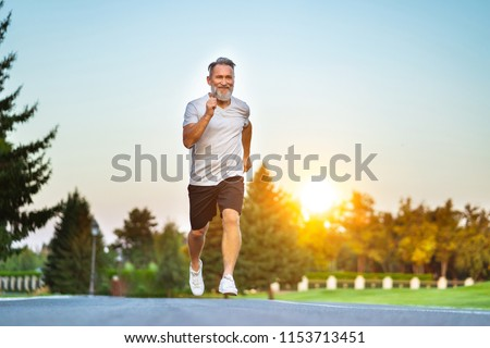 The elderly man running on the road on the sunrise background