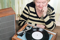 The elderly woman sitting at the table and listening to music retro from a vintage turntable