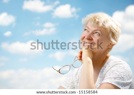 The elderly woman smiles and holds in hands glasses on a background of the blue sky