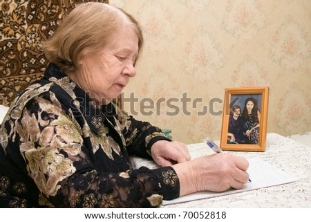 The elderly woman writes the letter to relatives