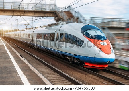 The electric train drives at high speed at the station