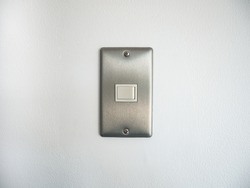 The electrical switch on the stainless steel frame is installed on a smooth white concrete wall.