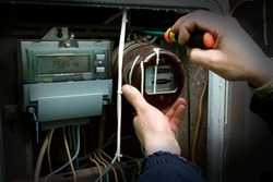 The electrician changes the old electric meter for the new.