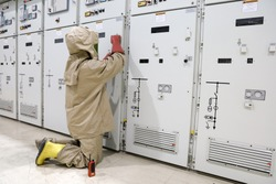 The electrician wear arc flash suit, electrical safety gloves and high voltage insulating boots to open power compartment door for rackout circuit breaker of medium voltage switchgear