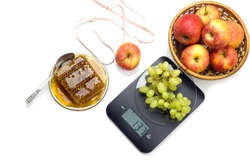 The electronic, black kitchen scale, apples, grape and centimeter close-up