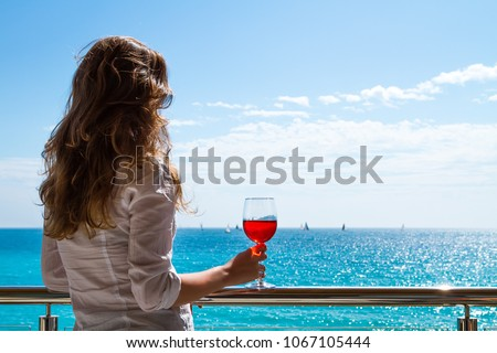 The elegant woman holding a glass of red wine with the background of a sunny seaside view.