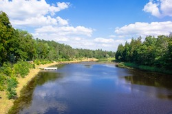 The embankment is overgrown with forest and a pantone bridge across the river. Bank of the Ogre river in the town of Ogre. Countryside and nature of Latvia.