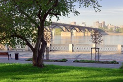 The embankment of the river Ob. The view from the Park at St. Michael the embankment on the bridge and tall buildings on the horizon. A bench, a paved path without people, a lattice fence