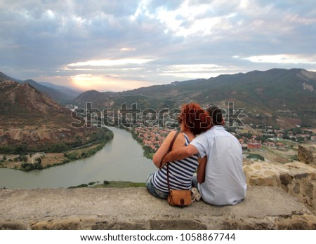 The embracing couple on the survey platform of Jvari Monastery near the city of Mtskheta in Georgia against the background of a sunset over confluence of Aragvi and the Kura #1058867744