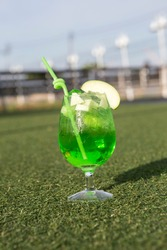 The Emerald Green drink cocktail perfect balanced of Midori and green apple juice in an iced beverage glass garnish with fresh apple dices and fancy spiral green straw. Blur outdoor garden background.