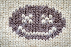 The emoticon smiles. Knitted from woolen threads.