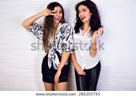 The emotion of joy. Two young girls looking at the camera smiling, clothing Black and White, standing against a white wall. having fun together.
