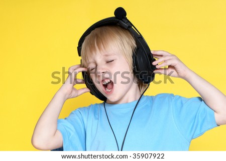 The emotional kid in ear-phones on a yellow background