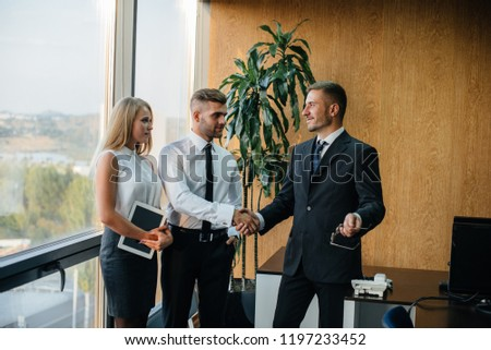 The employees of the firm are discussing the contract standing near the window. Business. Office. Finance. #1197233452