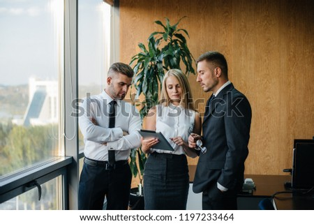 The employees of the firm are discussing the contract standing near the window. Business. Office. Finance. #1197233464