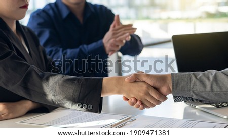 The employer shook hands to congratulate the new employee in the interview after meeting in the office with a friend clapping and rejoicing at the job interview idea.