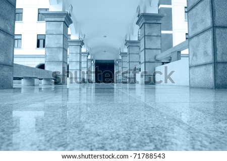 the empty hall of a very large high school building, blue tone.