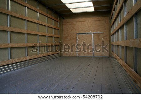 The empty interior of the back of a moving truck.
