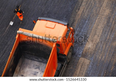 The empty orange truck. Road works flooring asphalt laying. Top view and a uniformed worker.