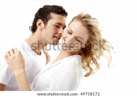 The enamoured young couple embraces on a white background