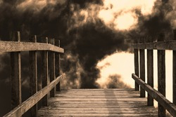 The end of a wooden bridge leading towards a drop. Billowing dark smoky clouds and glowing light give a sense of hell fire and apocalyptic doom.