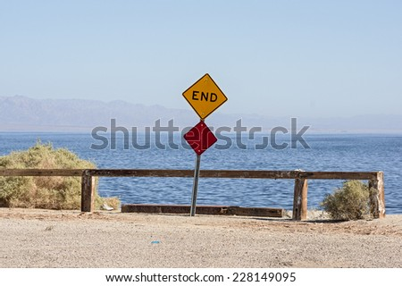 the end of the road where a road dead ends into the Salton Sea with a sign and barrier