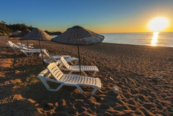 The end of the summer season on the Turkish coast of the Mediterranean with empty sunbeds on the beach with warm sun rays.
