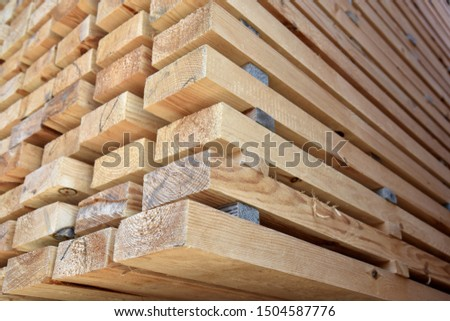 The end part of the dried wooden beam is piled in a pile in the warehouse.