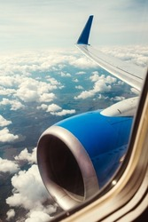 The engine and wing of an airplane in the sky during flight - the view from the airplane window to the ground before landing