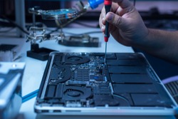 The engineer repairs the laptop and the motherboard.
