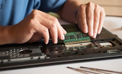 The engineer repairs the laptop (pc, computer) and the motherboard. Installs the equipment (ram)