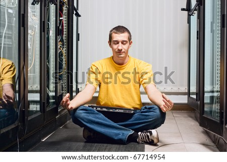 The engineer siting in datacenter near telecomunication equipment and relax - stock photo
