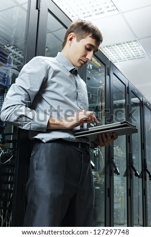 The engineer stand in data center near telecommunication equipment with tablet PC