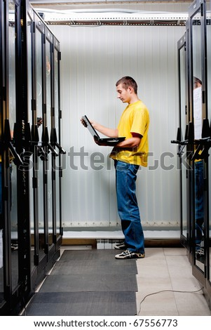 The engineer stand in datacenter near telecomunication equipment