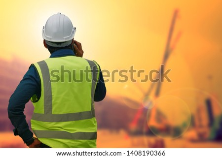 The engineer standing orders for construction crews to work on blurred site background. Industry and safety ideas concept. #1408190366