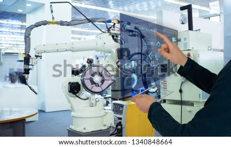 The engineer uses a futuristic projection touch screen to control robots in a smart factory. Smart industry 4.0 concept