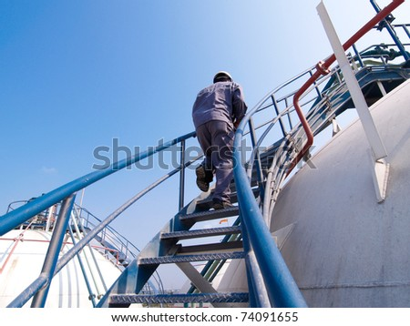 The engineer walking along the ladder of the refinery tank for checking valves and safety systems