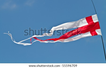 The English flag, the red cross of St George, flying as a pennant against a blue sky on a sunny day