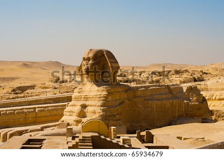 The entire full length profile of the Great Sphinx is seen in front of a clear blue sky and nobody present at the Giza Pyramids in Cairo, Egypt. Horizontal copy space