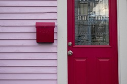 The entrance to a quaint country style cottage with a fuchsia colour antique decorative glass door, a vintage letterbox or postal box on a pink exterior clapboard wooden wall of a residence.