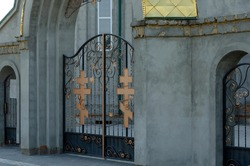 The entrance to the christian church is decorated with metal crosses. Forged gate to the church with orange crucifixes. Orthodox Church. Symbol of faith.