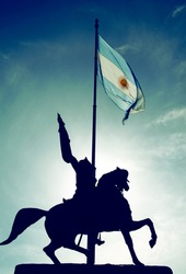 The Equestrian monument to General Manuel Belgrano, a landmark of Buenos Aires, and the Argentinian Flag in Buenos Aires, Argentina. It is located at Plaza de Mayo, in front of the Casa Rosada